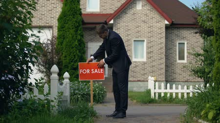 агентство : Male owner installing for sale signboard in front of house entrance, real estate