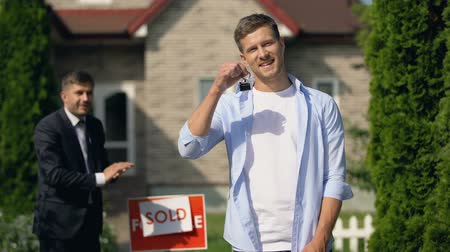 satılır : New home owner smiling, showing keys, broker changing inscription on signboard
