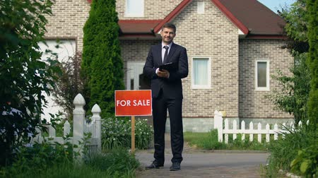 vacant : Smiling real estate broker holding documents with information for clients, sale