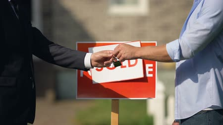 sallama : Man taking house keys and shaking hand of estate agent, successful deal, sale