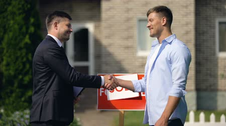 sallama : Real estate agent and new apartment owner shaking hands, celebrating good deal