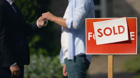 для продажи : Sold sign on for sale signboard, man taking keys and shaking hand to broker