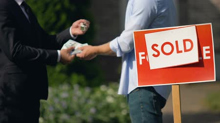 для продажи : Estate agent and man exchanging money and house keys against sold signboard