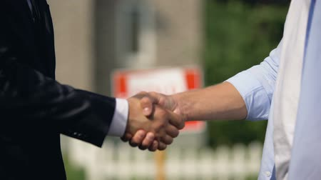 sallama : Two man shaking hands on background of sold signboard, successful house buying