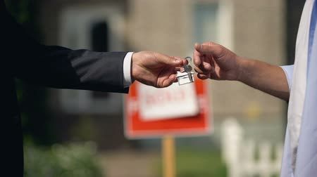 для продажи : Letting agent giving keys from apartment to new owner against sold signboard Стоковые видеозаписи