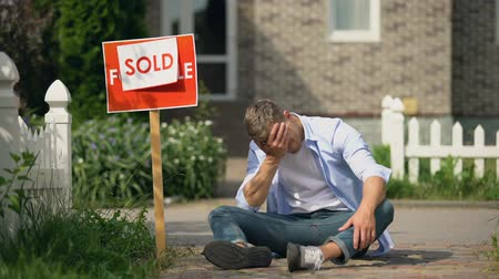 housing problems : Male crying sitting on ground near sold signboard, state takes property for debt