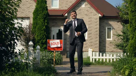 проданный : Estate agent in business suit showing yes gesture standing in front of sold home