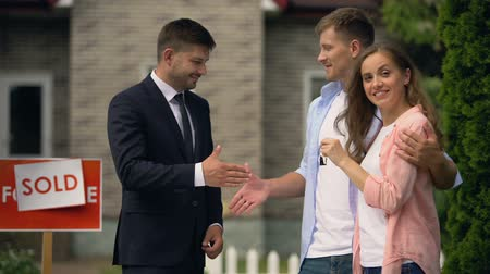 credit : Estate agent giving house keys to woman and shaking hand of man, good deal