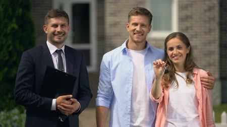 проданный : Smiling realtor with documents and happy couple with keys posing near house
