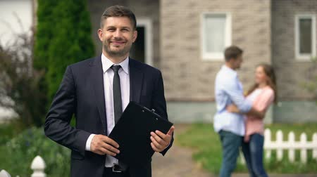 tehcir : Smiling broker standing with documents, happy family hugging near their new home