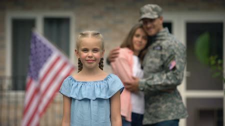 bandeira americana : Little girl showing american flag strike in front of parents, patriots family
