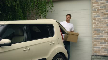 belongings : Casual male putting cardboard box in car, moving in new house, real estate Stock Footage