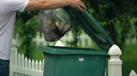separado : Male citizen throwing garbage in trash can, preventing littering, environment Stock Footage