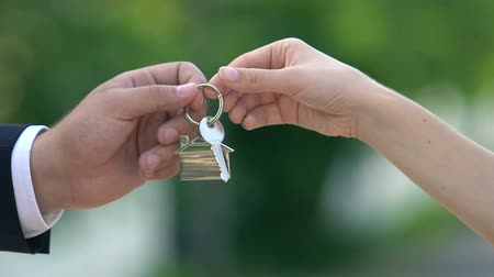 bérlet : Female hand taking house key from real estate agent, apartment rent, property