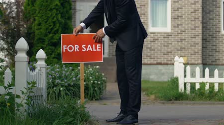 mülkiyet : Real estate broker in suit setting for sale sign front of house, agency service Stok Video