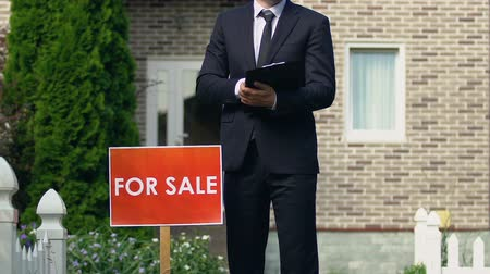 mülkiyet : Smiling male broker suit standing near for sale sign outside house, occupation Stok Video