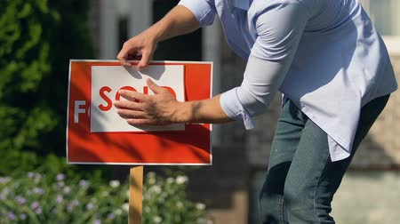 проданный : Young man setting sold sign front of building, property sell service, ownership
