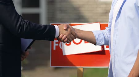 проданный : Sales agent and young man shaking hands on sold sign background, agency service