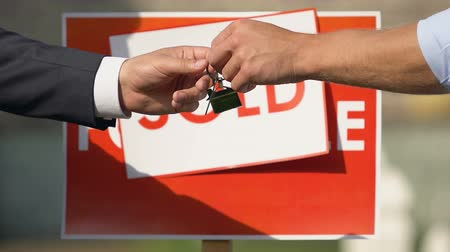 sallama : Real estate broker giving house key and shaking hands, sale agreement approval Stok Video