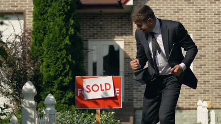 bérlet : Male real estate agent setting sold sign showing yes gesture, successful deal Stock mozgókép