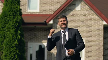 bérlet : Caucasian young broker showing success gesture standing outside house, deal