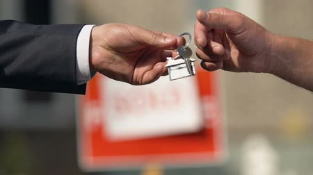 makler : Male hand taking apartment key from broker sold sign background, agency client