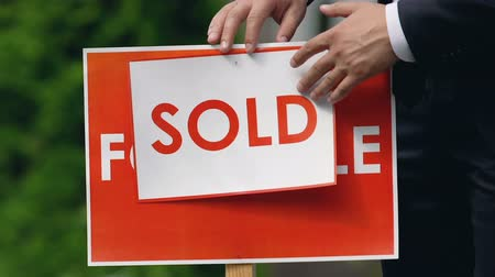 проданный : Male agent setting sold sign outdoors, real estate company, house ownership