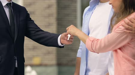 makler : Real estate salesman giving key to young couple and shaking hands, family house Wideo
