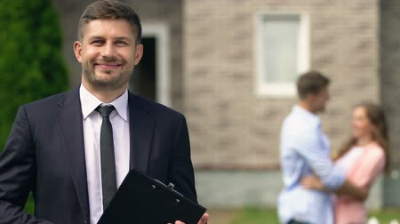 komisyoncu : Professional real estate agent smiling camera, happy couple hugging background Stok Video