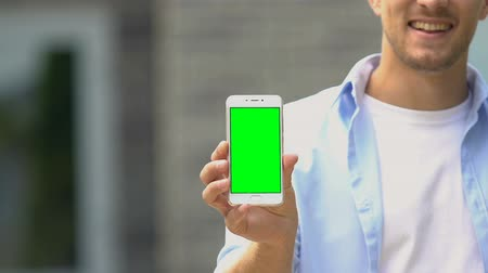 alpha cell : Cheerful young male showing smartphone green screen, online app, cash back Stock Footage