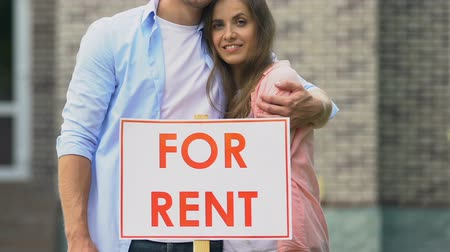 агентство : Smiling young couple standing behind for rent sign outside cottage, real estate