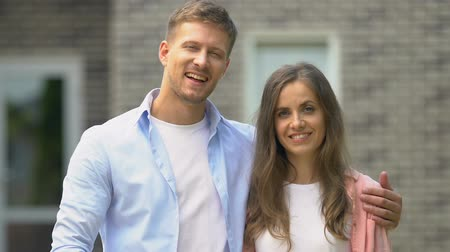 polegar : Smiling couple showing thumbs up standing outside house, real estate agency