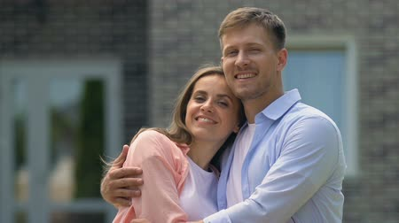 bérlet : Loving young couple hugging smiling on camera, tender relations, young family