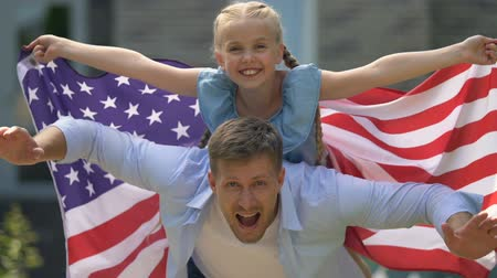 čtvrtý : Playful daughter and father with american flag, independence day, celebration