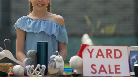 relocate : Smiling girl yard sale sign on table, child selling unused things, neighborhood Stock Footage