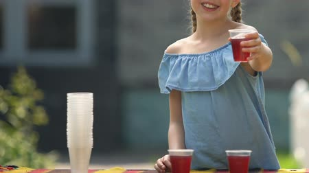stroop : Joyful girl showing juice plastic glass, selling refreshing syrup outdoors drink