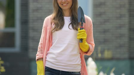 kielnia : Cheerful housewife in rubber gloves holding garden trowel outside house, hobby