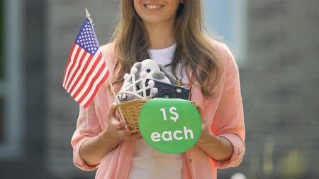 пригород : Smiling woman holding stuff basket with 1 dollar each sign and american flag