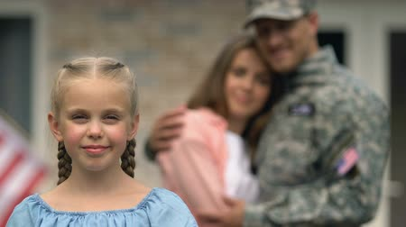 coming home : Smiling girl showing american flag patch, hugging parents on background, patriot Stock Footage