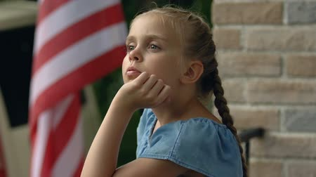 remember : Sad girl missing father standing house balcony, american flag background patriot