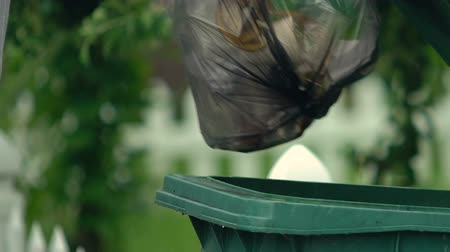 arrumado : Man throwing garbage bag in green plastic container, waste utilization, ecology
