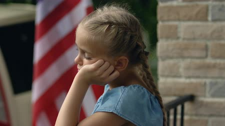 bandeira americana : Unhappy female child standing outdoors american flag background, feeling lonely Vídeos