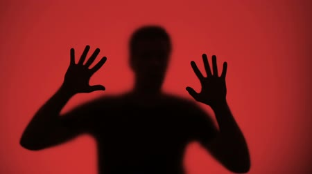 ter cuidado : Injured male silhouette behind glass, red lights blinking on background, warfare
