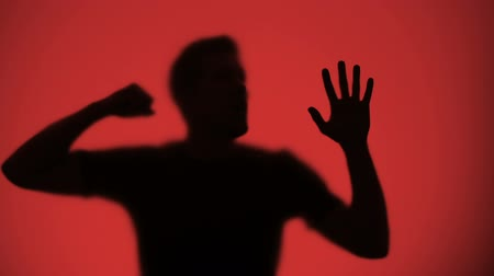 knock : Male silhouette knocking on glass, red lights blinking on background, warfare