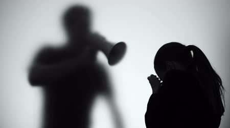 öfkeli : Silhouette of man shouting on crying woman in megaphone, family problems Stok Video
