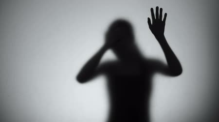 abuse : Silhouette of desperate woman crying behind glass, mental disorder, hysteric