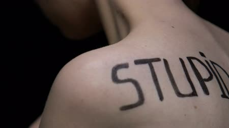 abuse : Stupid written on female body closeup, suffering young woman turning back, abuse