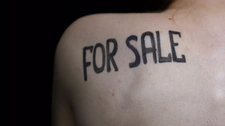 írott : For sale written on female body closeup, human trafficking victim, hopelessness