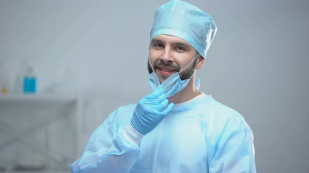 soins intensifs : Smiling surgeon taking off medical face mask after successful operation, work