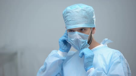 körülmények : Professional surgeon in uniform wearing medical face mask before operation